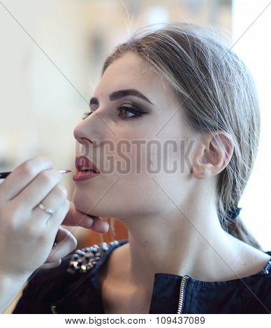 Closeup of a makeup artist applying makeup poster
