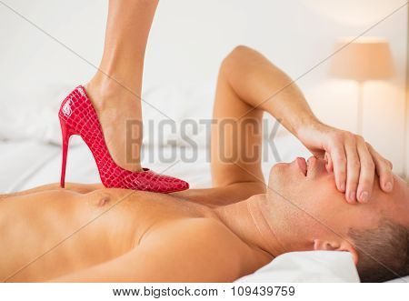 Man holding  his eyes covered and  trying to resist sexy woman with high heels