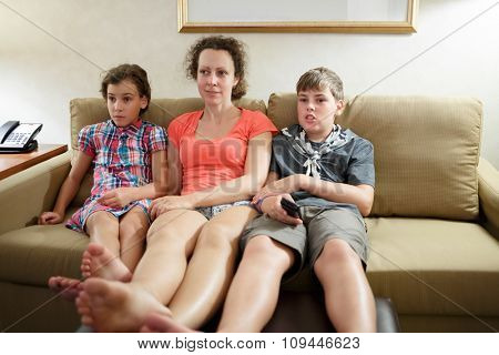mother with two children watching tv on a coach
