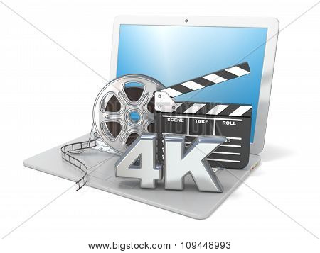 Laptop with film reels movie clapper board and 4K video icon