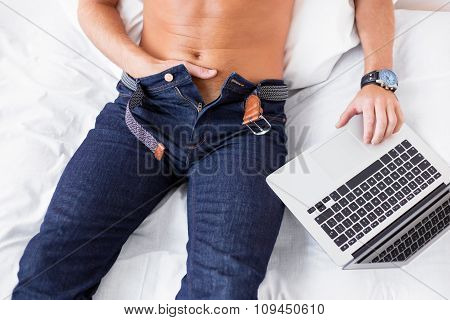 Man masturbating while using laptop