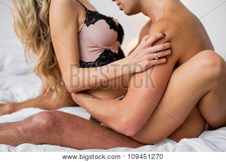 Man kissing woman's breasts