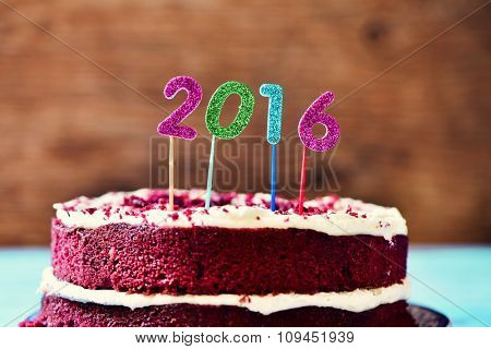 closeup a red velvet cake topped with four glittering numbers of different colors forming the number 2016, as the new year