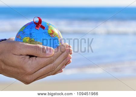 closeup of the hands of a young caucasian man holding a world globe with a red ribbon, for the fight against AIDS