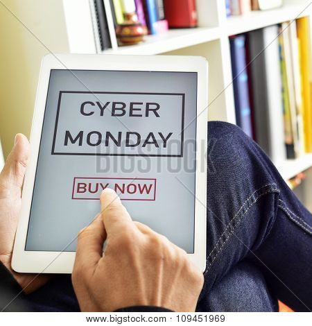 closeup of a young caucasian man sitting in an armchair pressing the button buy now in a tablet computer with the text cyber monday in its screen poster