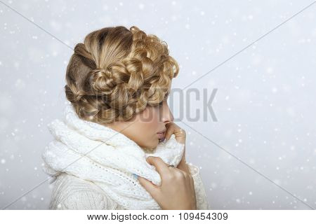 portrait of a beautiful young blonde woman on a light background. hair tied in a braid. girl wearing a warm sweater and scarf. copy space. poster