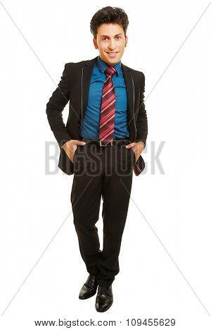 Young business man in apprenticeship standing frontal with hands in his pockets