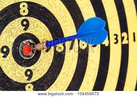 Lucky concept: photography success hitting target aim goal Blue Dart in bull's eye.