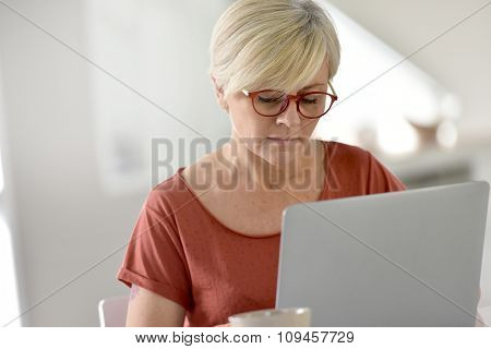 Senior woman at home using laptop computer