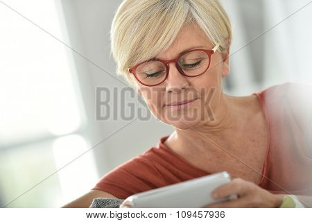 Senior woman with eyeglasses websurfing on smartphone poster