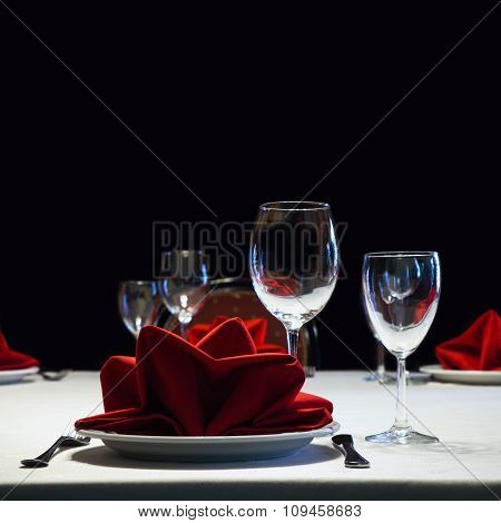 Served table. Romantic restaurant interior with a bright tablecloth, napkins, wine glasses and cutle