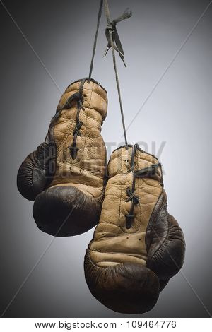 a pair of worn boxing gloves hanging on the string