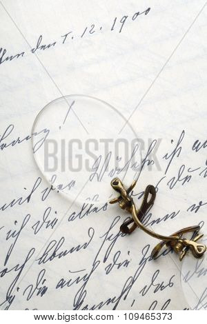 pair of rimless glasses on a vintage letter