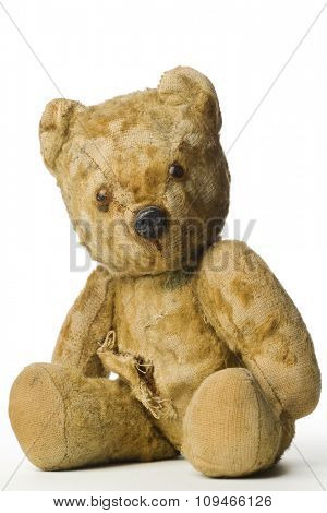 an old and shabby vintage teddy bear on white