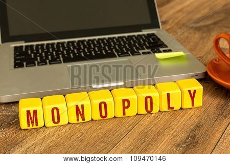 Monopoly written on a wooden cube in a office desk