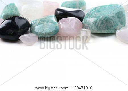 Pile of stones: pink quartz, azonite, black onyx and rock crystal isolated on white background