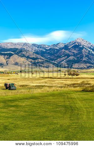 An old truck in a field at the foot of the Bridger mountain range in Belgrade Montana poster