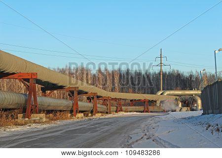 Large pipelines along the road in winter poster