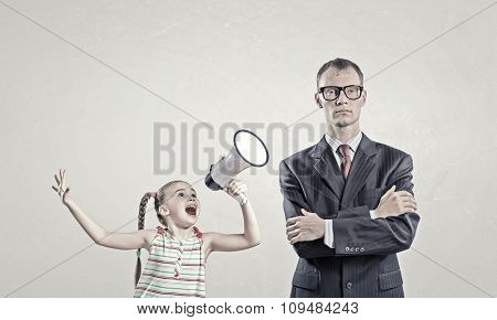Child screaming with megaphone to adult indifferent man