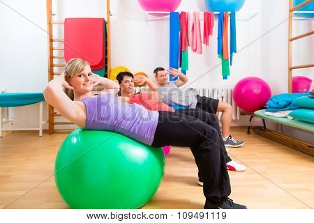 Patients at the physiotherapy doing physical exercises with therapist on training balls poster