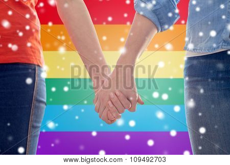 people, homosexuality, same-sex marriage, gay and love concept - close up of happy lesbian couple holding hands over rainbow flag background over snow effect