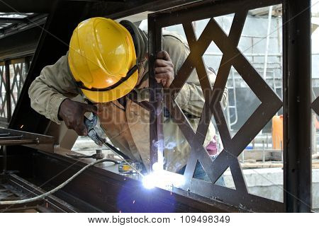 Welders welded the decorative mild steel at the construction site