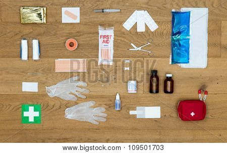 The items and objects in a first aid kit, neatly aligned on a wooden surface, including pliers, bandages, plaster, pills, heat or cold pack, isolation blanket, tape, rubber gloves,  and much more.