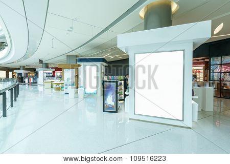 blank billboard in hallway of modern shopping mall