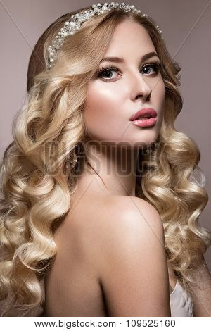 Beautiful blonde in a wedding image with curls, light lips and tiara. Beauty face.