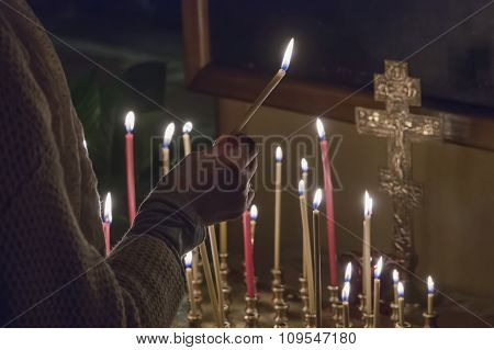 Woman lighting prayer candle in a church