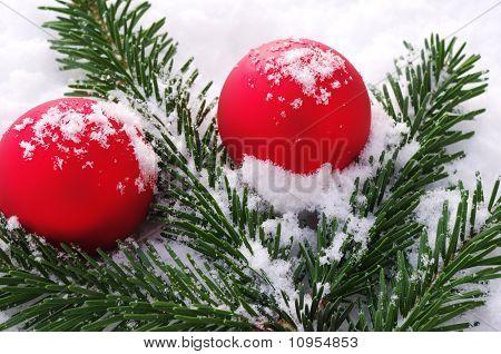 Red christmas tree balls and snow