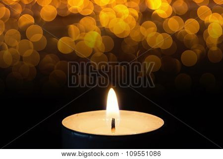 Burning tealight in darkness with bokeh