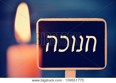 closeup of a chalkboard with the word Hanukkah, the Jewish Festival of Lights, written in Hebrew and a lit candle