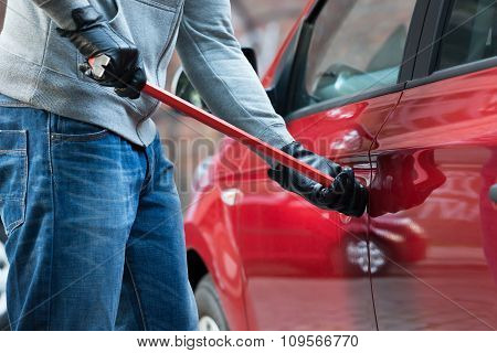 Thief Opening Car's Door With Crowbar