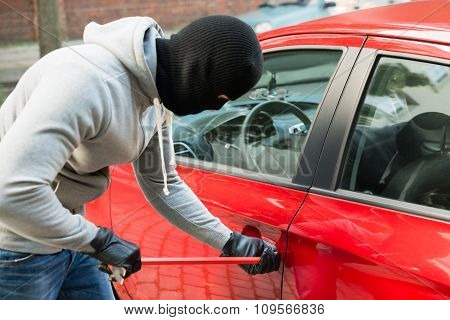 Thief With Mask Using Crowbar To Open Car's Door