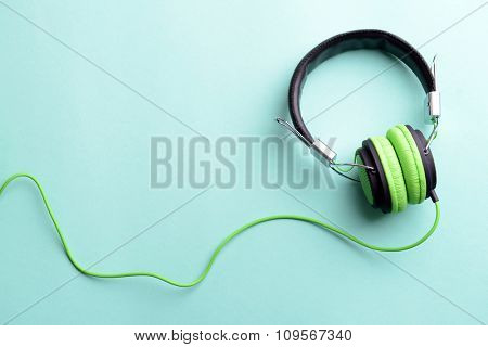 A pair of green-black headphones, on blue background