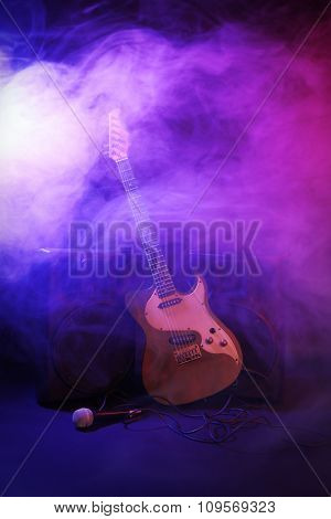 Big loudspeakers with electric guitar and microphone in dense smoke under purple light