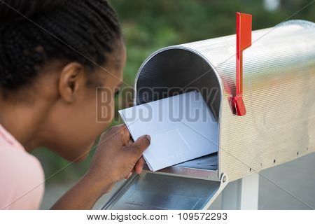 Woman Putting Letter In Mailbox
