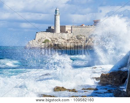 The Morro Castle in Havana with a stormy ocean and big waves crashing on the seawall