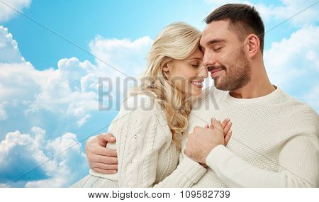 family, love, happiness, affection and people concept - happy couple cuddling over blue sky and clouds background poster