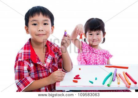 Little asian children playing and creating toys from play dough on table. Boy and girl smiling and show works from clay at camera over white background. Strengthen the imagination of child poster