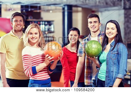 people, leisure, sport, friendship and entertainment concept - happy friends in bowling club poster