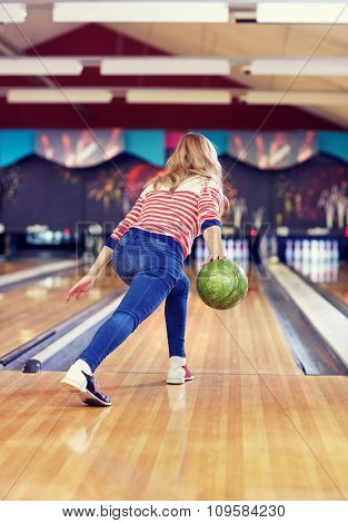 people, leisure, sport and entertainment concept - happy young woman throwing ball in bowling club poster