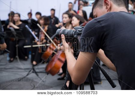 Asian cameraman filming an outdoor live classic concert music