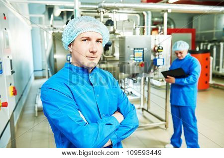 Two pharmaceutical technician male workers operating water preparation production line at pharmacy industry manufacture factory using notebook computer