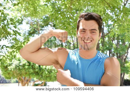 Young hispanic man showing his arm biceps muscles. Fitness mal at the park. poster