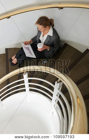 Businesswoman Preparing For Meeting In Stairwell