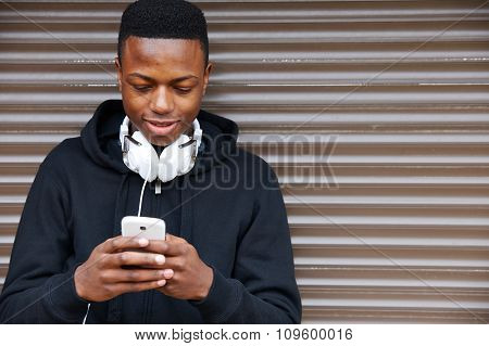 Teenage Boy Listening To Music And Using Phone In Urban Setting