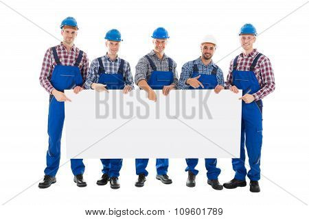 Confident Male Construction Worker Holding Blank Billboard