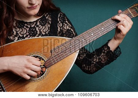 female playing lute string instrument